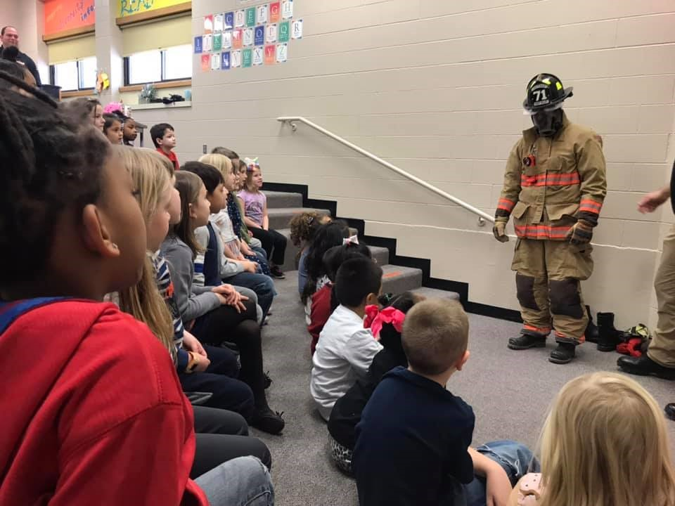 Fire fighter in turnout gear helping children be less scared