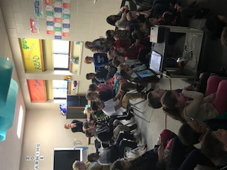 1st & 2nd graders listening to author